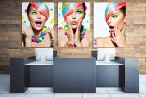 Biuro z biurkiem, dwoma komputerami oraz trzema obrazami na płótnie przedstawiającymi modelki o kolorowych włosach i biżuterii.