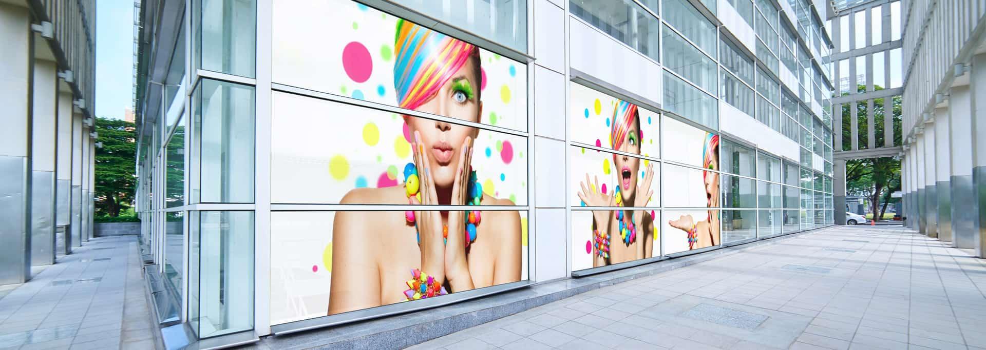 Szary nowoczesny biurowiec, którego okna są ozdobione kolorowymi naklejkami przedstawiającymi zdziwioną kobietę.