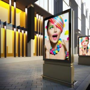 Kaseton znajdujący się na ulicy, przy biurowcu, przedstawiający zdziwioną kobietę w kolorowej charakteryzacji.