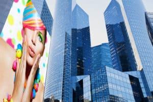 Siatka mesh znajdująca się na wieżowcu, przedstawiająca kobietę w kolorowej charakteryzacji.