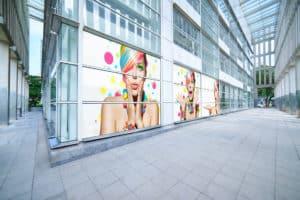 Szary biurowiec ozdobiony barwnymi naklejkami przedstawiającymi zdziwioną kobietę