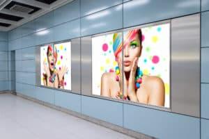 Plakat wielkoformatowy przedstawiający kobietę w barwnej stylizacji, znajdujący się w miejscu publicznym