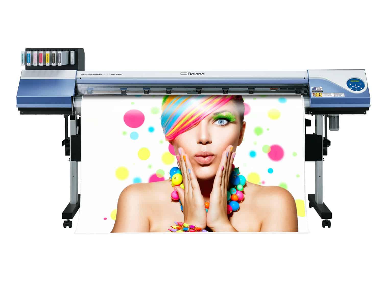 Drukarka wielkoformatowa drukująca baner przedstawiający kobietę z kolorowymi włosami.