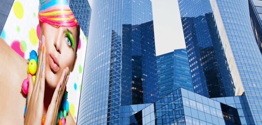 Znajdująca się na wieżowcu w wielkim mieście, siatka mesh przedstawiająca kobietę o kolorowych włosach.
