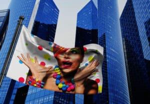 Flaga reklamowa powiewająca na wietrze na tle wieżowców przedstawiająca zaskoczoną modelkę w kolorowej stylizacji.